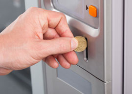Coin being inserted into a vending machine.