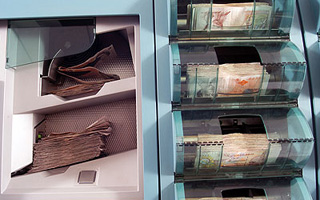 Our business: Pre issue image featuring a banknote processing machine.