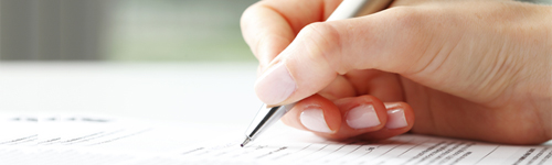 Image of person writing holding a pen.