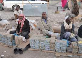 Somalian men sit beside stacks of banknotes in market.
