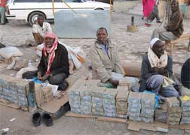 Somalian men sit beside stacks of banknotes in market.