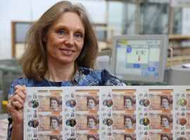Image of Bank of England Chief Cashier Victoria Cleland holding a sheet of ten pound banknotes.